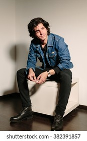 Young man in a jeans jacket holds a cigarette in hand and sits on the ottoman.