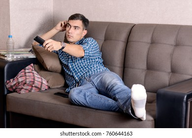 A young man in jeans, with a remote control for the TV boredom on the face changes the channel.