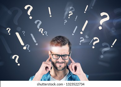 Young man in jeans shirt and glasses thinking hard sanding near gray wall with question and exclamation marks on it.