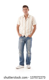 Young man in jeans and shirt standing with hands in pocket.