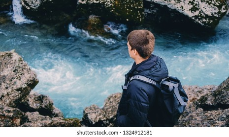 Young man in jeans standing under Niagara Waterfall on the river Cijevna in Podgorica, Montenegro