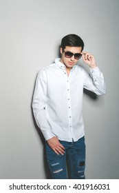 Young man in jeans and white shirt standing near the wall with glasses
