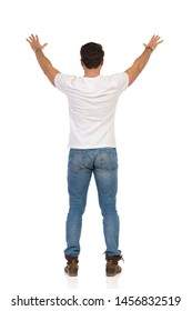 Young man in jeans and white t-shirt is standing with arms raised and waving hands. Rear view. Full length studio shot isolated on white.