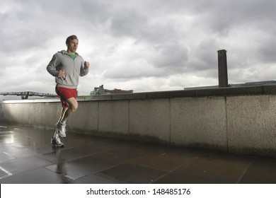 Young man jogging besides the Thames river in London on a stormy day