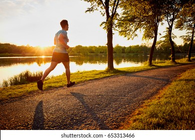 Young man jogging in park during sunset