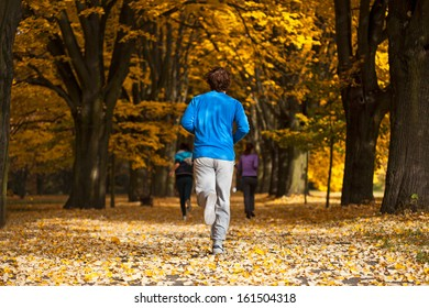 Young man jogging in the park, fall time