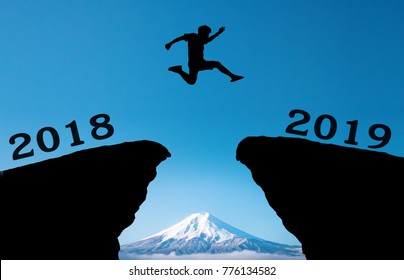 A young man jump between 2018 and 2019 years over the sun and through on the gap of hill silhouette evening colorful moutain. happy new year 2019.