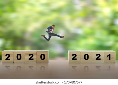 Young man jump from number 2020 to number 2021 on nature blurred background , Happy new year concepts.