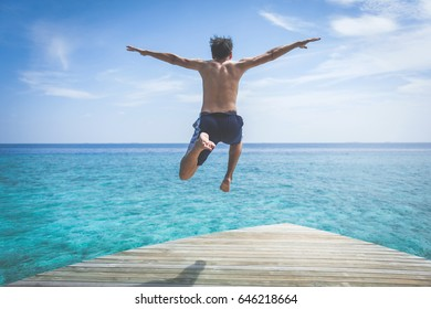young man jump on the sea