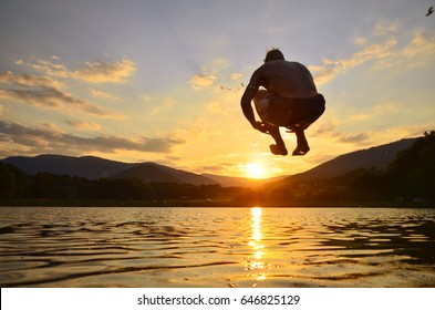 Young man jump onto summer water during calm sunset