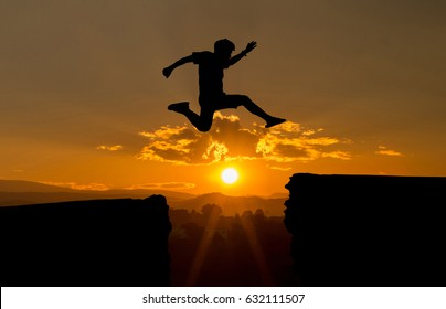 young man jump over the sun and through on the gap of hill silhouette evening colorful sky.image for spirit brave concept.man is representative of success in the past and gold for the future in 2019