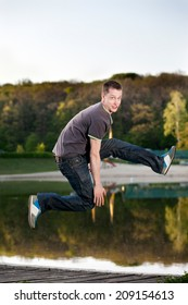 The young man jumped up on a background of lake