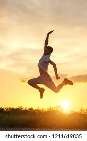 young man jumping up against the sunset sky.