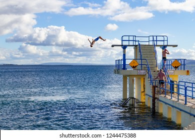 Young man jumping in Blackrock Beach in Salthill, Galway, Ireland