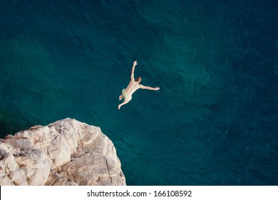 Young man jumping from cliff into sea.