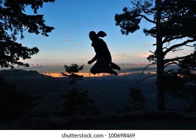young Man jumping at Grand Canyon, Arizona, USA