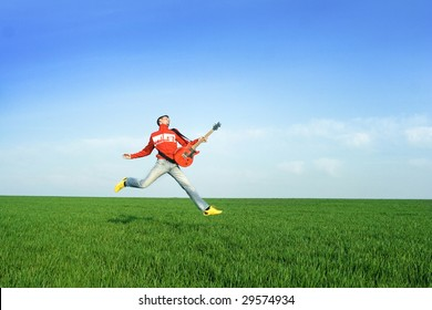 Young man jumping with guitar i meadow