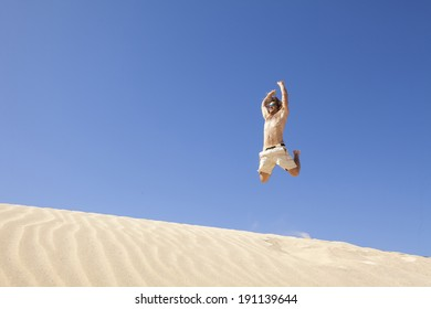 young man jumping happy in the desert