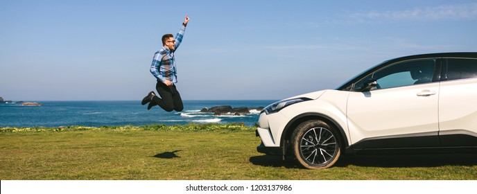 Young man jumping happy in front of a car outdoors