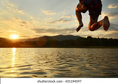 Young man jumping into the lake during calm summer sunset.
