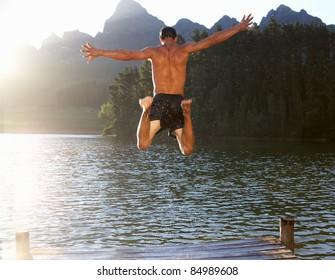 Young man jumping into lake