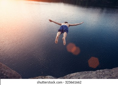 Young man jumping into the water from cliff at sunset with outspread hands (intentional sun glare and lens flares, man in motion blur)