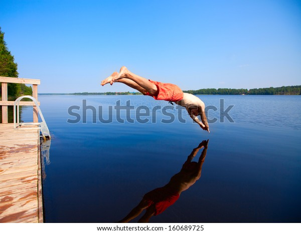 Young man jumping into water