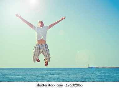 young man jumping with joy at the sea