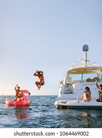 Young man jumping off the boat in to the sea. Young people having fun during party on a private boat. Men and women on yacht and inflatable toy in sea.