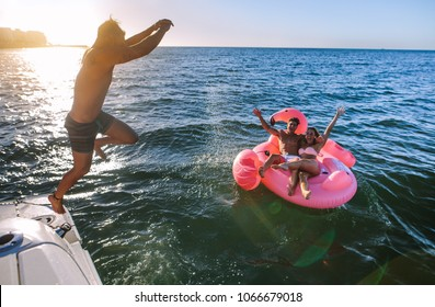 Young man jumping off a boat with friends sitting on inflatable top in the sea water. Friends having fun on their summer vacation.