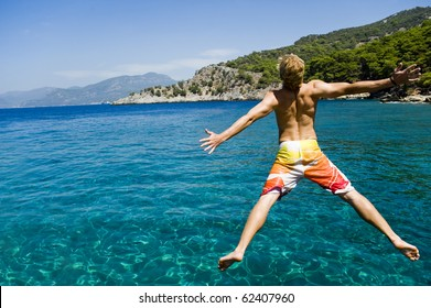 Young man jumping off a boat, enjoying the freedom of his summer holiday