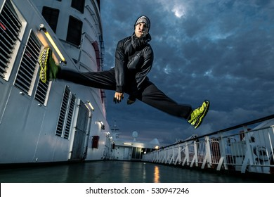 Young man jumping on the deck and making the split.