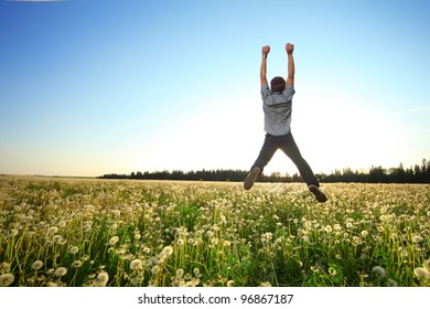 Young man jumping on a green meadow over blue clear sky background