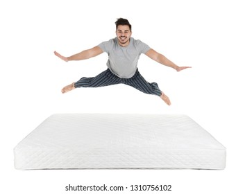 Young man jumping on mattress against white background