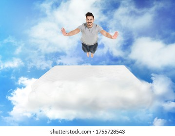 Young man jumping on mattress in clouds