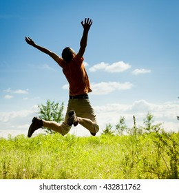 Young man jumping on meadow  on clear blue sky background