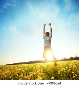 Young man jumping on meadow with dandelions on cloudy background
