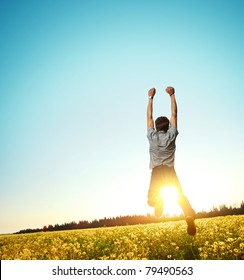 Young man jumping on meadow with dandelions on clear blue sky background