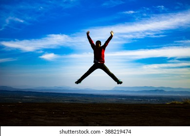 young man is jumping on top of the mountain