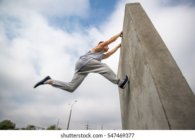 young man jumping on the walls sport parkour