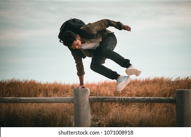 Young man jumping over fence