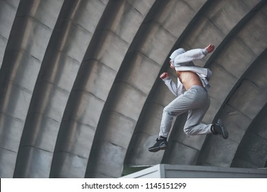 A young man is jumping. Parkour in urban space, sporting activity