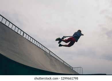 Young man jumping, performing tricks and skills on ramp with kick scooter at city park on extreme skatepark. Guy makes an extreme jump and flying off in the air on a scooter. Recreation concept.