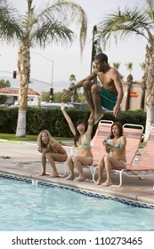 Young man jumping in the pool with friends sitting at pool side