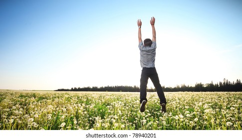 Young man jumping with raised hands over meadow with dandelions