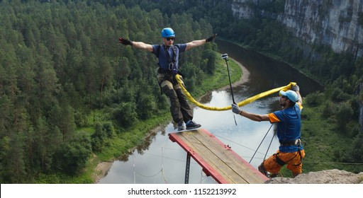 Young man jumping with a rope from a great height into the deep canyon on the background of the forest and river below, panorama. Ropejumping.