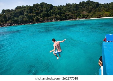 young man jumping to the sea from yacht near the beach of paradise island