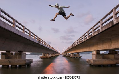 A young man jumps from a bridge. To the other side of the bridge.