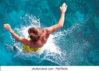 a young man jumps into the turquoise water of the Red Sea