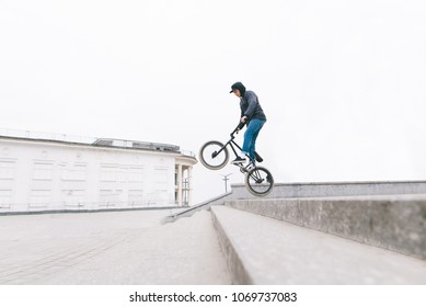 A young man jumps on a BMX bike along the stairs. Bmx freestyle on the background of the urban landscape. BMX concept.